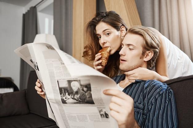 Atrakcyjna śliczna żona stoi blisko męża, czytając jego gazetę i jedząc rogalika, jednocześnie przytulając go od tyłu. dziewczyna jest znudzona i zainteresowana tym, co chłopak teraz czyta
