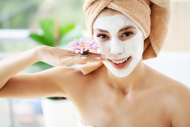 Atrakcyjna śmieszna kobieta z glinianą maską na twarzy.
