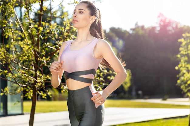 Atrakcyjna sportowa kobieta w odzieży sportowej biegnie w parku w słoneczny dzień