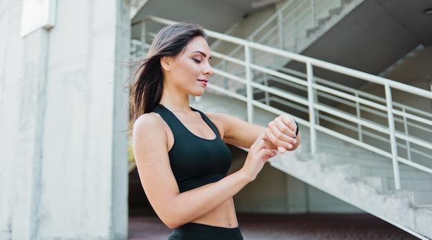 Atrakcyjna sportowa kobieta w odzieży sportowej używa inteligentnego zegarka na zewnątrz w środowisku miejskim