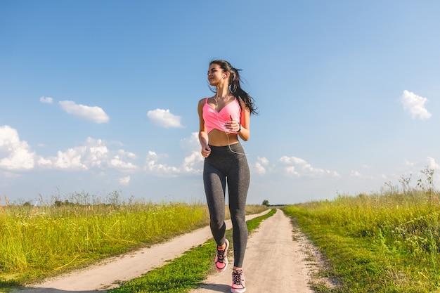 Atrakcyjna sportsmenka biegająca po ścieżce w terenie