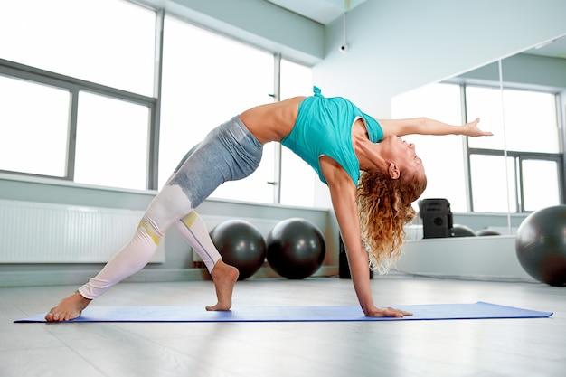 Atrakcyjna sportsmenka robi ćwiczenia na podłodze w nowoczesnym studio podniebień piękna, sportowa dziewczyna utyka i wyciąga nogi i ręce