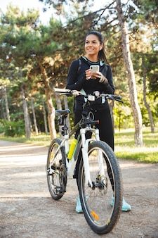 Atrakcyjna sportsmenka wysportowana z rowerem w parku, słuchająca muzyki przez bezprzewodowe słuchawki, za pomocą telefonu komórkowego
