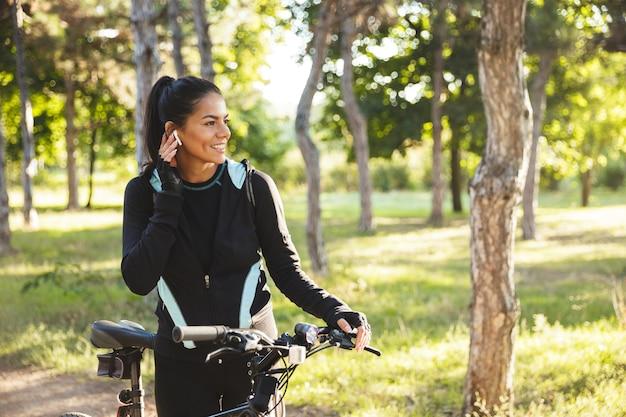 Atrakcyjna sportsmenka wysportowana z rowerem w parku, słuchająca muzyki przez bezprzewodowe słuchawki