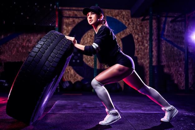 Atrakcyjna, sprawna kobieta lekkoatletka pracująca z ogromną oponą, obracająca się i rzucająca na siłowni. wysportowana kobieta ćwiczy z dużą oponą