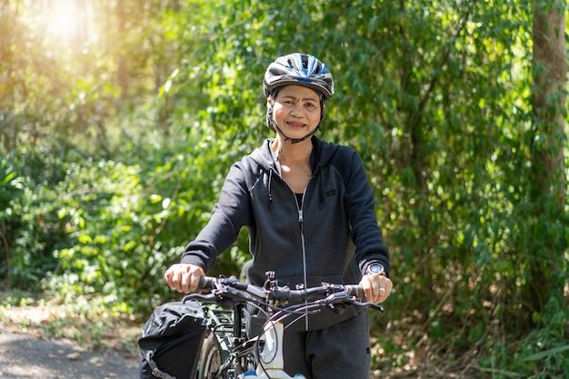 Atrakcyjna starsza azjatykcia kobieta z bicyklem w parku