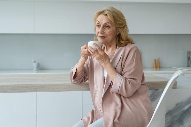 Atrakcyjna starsza kobieta delektująca się filiżanką kawy w kuchni myśląca z uznaniem