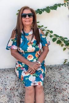 Atrakcyjna starsza kobieta nosi okulary, opierając się o białą ścianę.