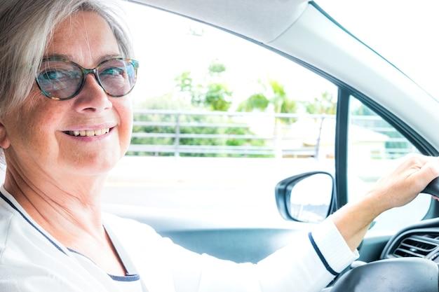 Atrakcyjna starsza kobieta patrzy na kamerę podczas jazdy samochodem. siwe włosy i okulary