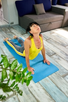 Atrakcyjna starsza kobieta pracująca w domu, robi joga lub pilates ćwiczy