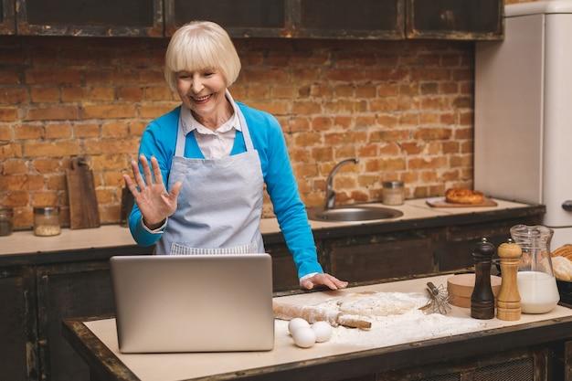 Atrakcyjna starsza kobieta w wieku gotuje w kuchni. babcia co smaczne pieczenia. za pomocą laptopa.
