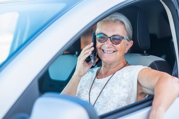 Atrakcyjna starsza kobieta zaparkowana swoim samochodem i używająca smartfona rozmawiającego i uśmiechającego się - aktywne osoby starsze