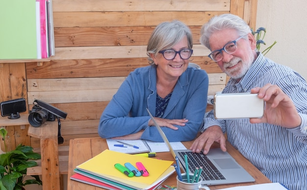 Atrakcyjna starsza para uśmiechająca się do selfie siedząca na świeżym powietrzu przy laptopie