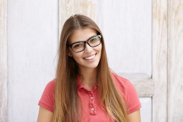 Atrakcyjna studencka dziewczyna z czarującym uśmiechem pozowanie