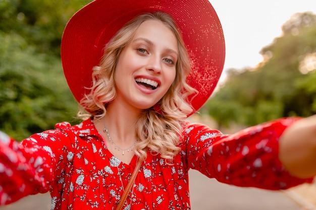 Atrakcyjna stylowa blond uśmiechnięta kobieta w słomkowym czerwonym kapeluszu i bluzce letnia moda strój robienie selfie zdjęcie