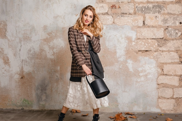 Atrakcyjna stylowa blondynka uśmiechnięta kobieta w kraciastej kurtce spaceru przed ścianą na ulicy