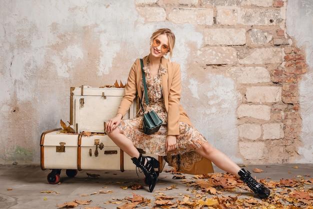 Atrakcyjna, stylowa blondynka w beżowym płaszczu siedzi na walizkach ścianę na ulicy