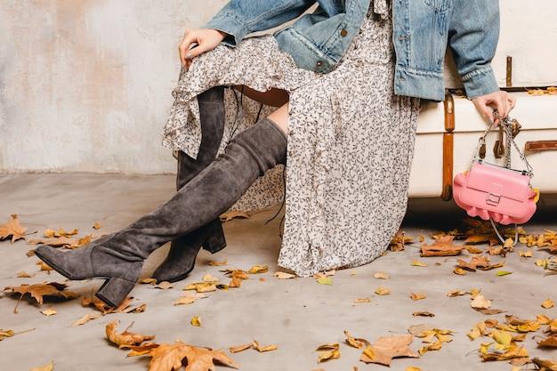 Atrakcyjna, stylowa blondynka w dżinsach i kurtce oversize, chodzenie przed ścianą na ulicy
