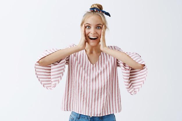 Atrakcyjna stylowa dziewczyna pozuje na białej ścianie