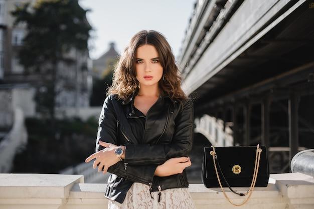 Atrakcyjna stylowa kobieta pozująca na ulicy w modnym stroju, zamszowej torebce, ubrana w czarną skórzaną kurtkę i białą koronkową sukienkę, wiosenno-jesienny styl