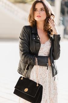 Atrakcyjna stylowa kobieta spacerująca po ulicy w modnym stroju, trzymająca zamszową torbę, ubrana w czarną skórzaną kurtkę i białą koronkową sukienkę, wiosenno-jesienny styl