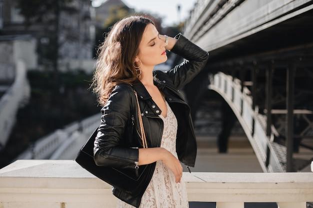 Atrakcyjna stylowa kobieta spacerująca po ulicy w modnym stroju, z zamszową torebką, ubrana w czarną skórzaną kurtkę i białą koronkową sukienkę, wiosenno-jesienny styl