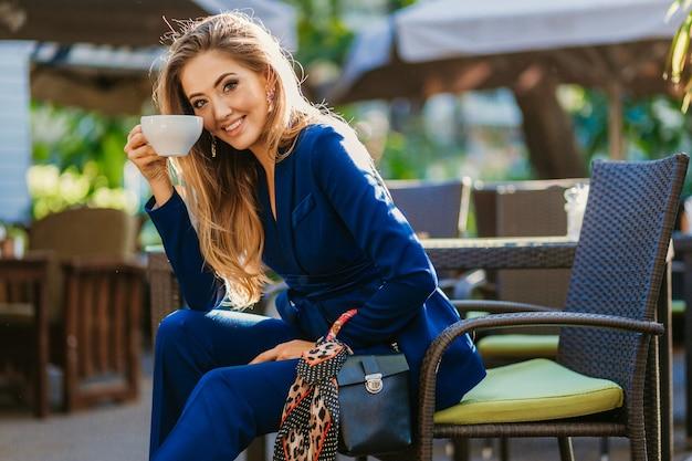 Atrakcyjna stylowa kobieta ubrana w niebieski elegancki garnitur siedzi przy stole w kawiarni filiżankę cappuccino
