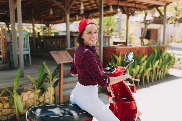 Atrakcyjna, stylowa młoda kobieta odwraca się i uśmiecha się podczas jazdy motocyklem w parku w słońcu