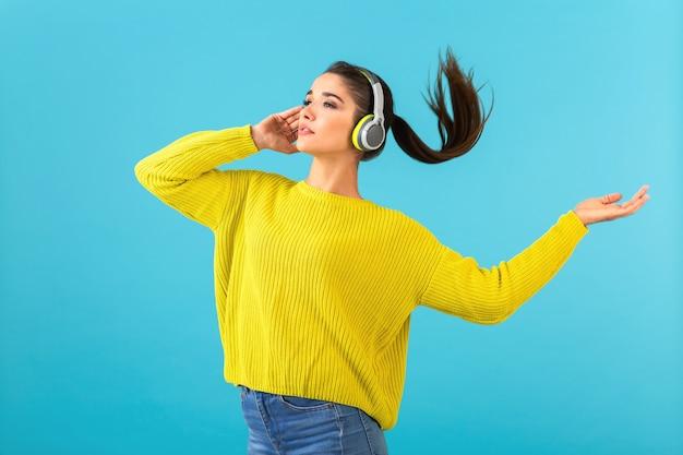 Atrakcyjna stylowa młoda kobieta słucha muzyki w słuchawkach bezprzewodowych szczęśliwa sobie żółty sweter z dzianiny kolorowy styl moda pozowanie