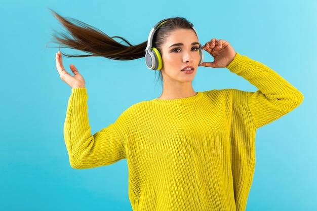 Atrakcyjna stylowa młoda kobieta słuchanie muzyki w słuchawkach bezprzewodowych szczęśliwy sobie żółty sweter z dzianiny