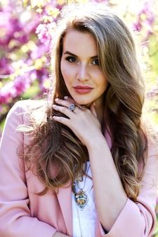 Atrakcyjna, stylowa młoda kobieta w lekkiej białej sukni, różowym płaszczu, z długimi włosami, spacery w ogrodzie z kwitnącą sakurą