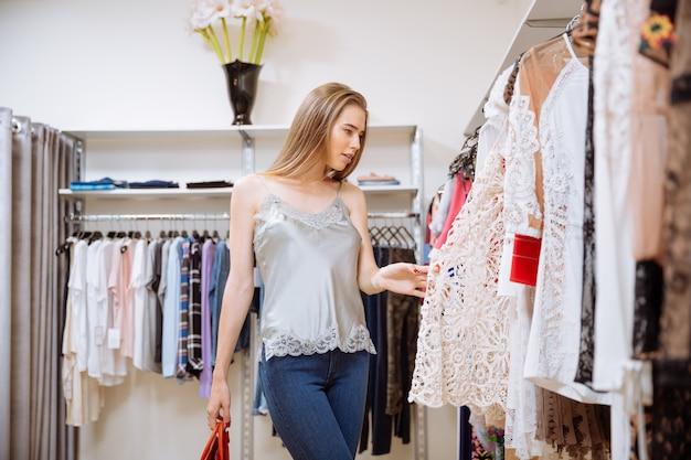 Atrakcyjna stylowa młoda kobieta wybiera ubrania w sklepie