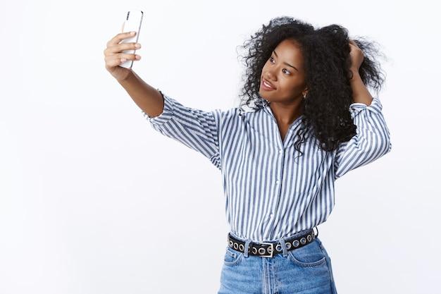 Atrakcyjna, stylowa, modna, pewna siebie, młoda, urocza, ciemnoskóra blogerka grająca w fryzurę, przechylająca głowę, zalotna, popisująca się postem, nowe zdjęcie online, trzymając smartfon, biorąc selfie wygląd wyświetlacz