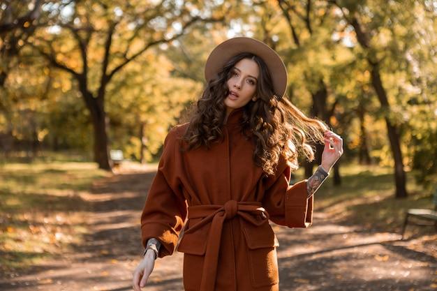 Atrakcyjna stylowa uśmiechnięta chuda kobieta z kręconymi włosami spacerująca po parku ubrana w ciepły brązowy płaszcz, jesień modny styl ulicy