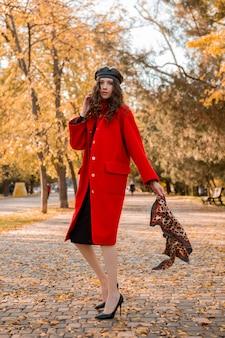 Atrakcyjna, stylowa, uśmiechnięta, chuda kobieta z kręconymi włosami spacerująca po parku ubrana w ciepły czerwony płaszcz modna jesień, styl uliczny, ubrana w beret i szalik w panterkę
