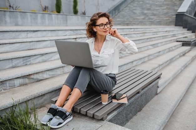 Atrakcyjna, stylowa uśmiechnięta kobieta w okularach, pisząca na laptopie