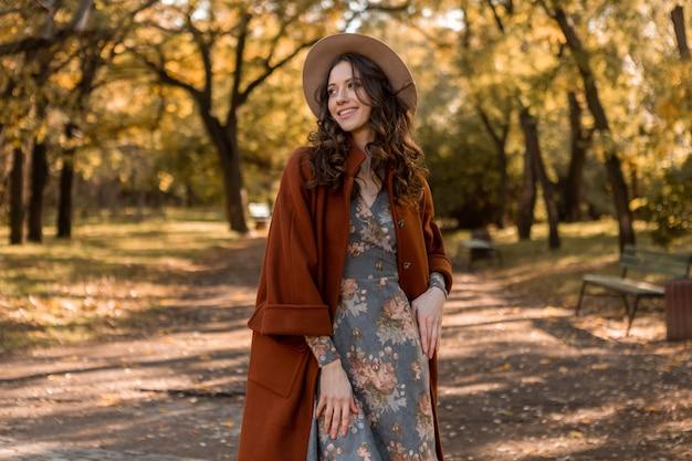 Atrakcyjna, stylowa uśmiechnięta kobieta z kręconymi włosami spacerująca po parku ubrana w drukowaną sukienkę i ciepły płaszcz jesień modna moda, styl uliczny