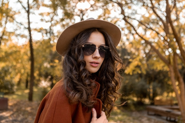 Atrakcyjna stylowa uśmiechnięta kobieta z kręconymi włosami spacerująca po ulicy w parku, ubrana w ciepły brązowy płaszcz jesień modna moda, styl uliczny w kapeluszu i okularach przeciwsłonecznych