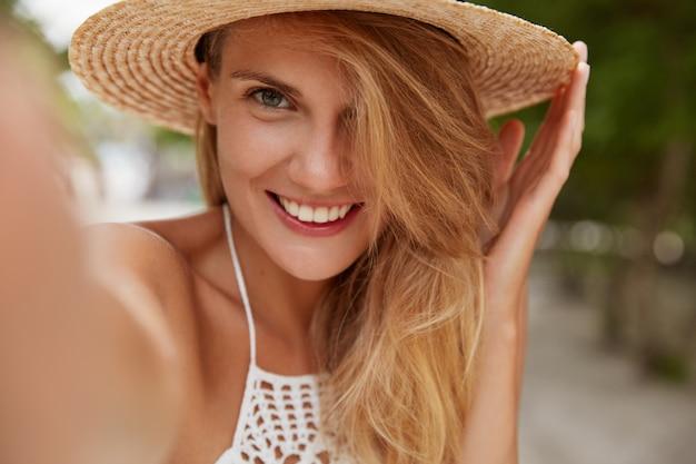 Atrakcyjna suczka o przyjemnym uśmiechu, jasnych włosach, w letnim kapeluszu, robi selfie z nierozpoznawalnym urządzeniem podczas spacerów na świeżym powietrzu, lubi piękne krajobrazy i ciepłą, świecącą pogodę. radosna kobieta