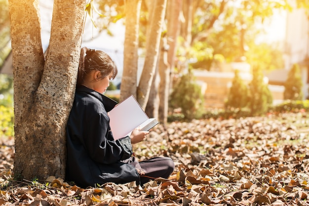 Atrakcyjna szczęśliwa azjatycka młoda dziewczyna cieszy się czytanie