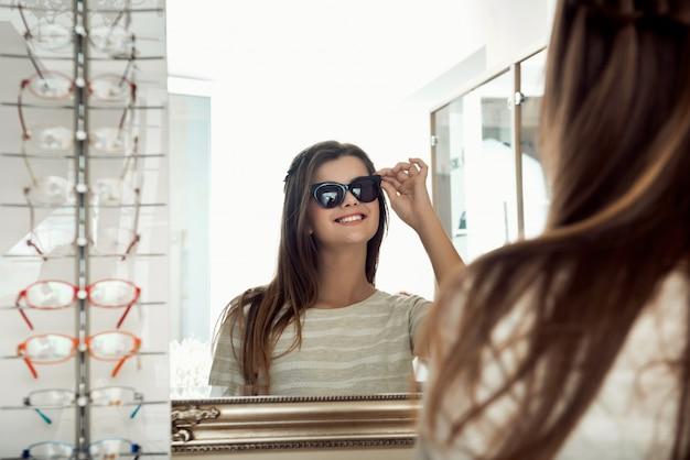 Atrakcyjna szczęśliwa brunetki kobieta patrzeje w lustrze podczas gdy próbujący na okularach przeciwsłonecznych w okulisty sklepie