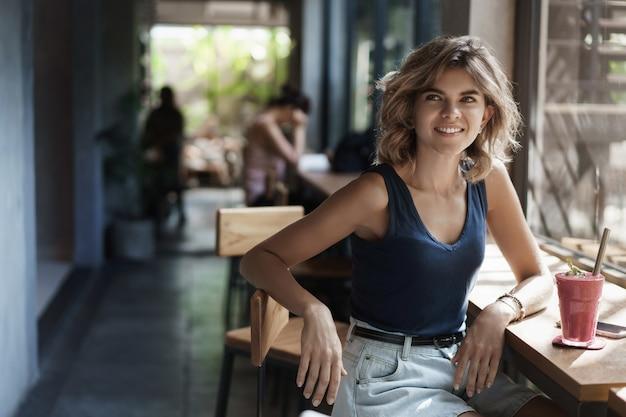 Atrakcyjna szczęśliwa dziewczyna pije smoothie dba o zdrowie, prowadzi aktywny tryb życia siedzieć przy oknie bar kawiarnia stolik zawrócić uśmiechnięty zachwycony czekać przyjść przyjaciela, spotkanie z restauracją partnera biznesowego.