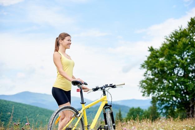 Atrakcyjna szczęśliwa dziewczyna rowerzysty pozycja na trawiastym wzgórzu z żółtym halnym bicyklem, cieszy się letniego dzień w górach. aktywność na świeżym powietrzu, koncepcja stylu życia