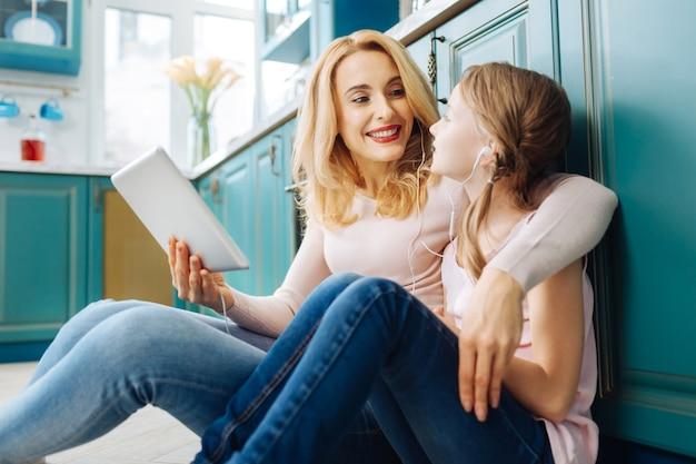 Atrakcyjna szczęśliwa jasnowłosa matka i córka, uśmiechając się i siedząc na podłodze w kuchni i słuchając muzyki