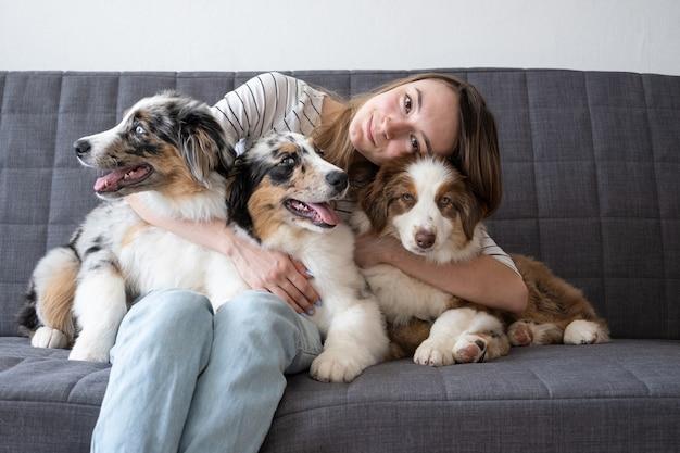 Atrakcyjna szczęśliwa kobieta przytulić trzy małe słodkie owczarek australijski niebieski merle czerwony trzy kolory szczeniak. siedząc na kanapie. koncepcja opieki nad zwierzętami. miłość między człowiekiem a zwierzęciem.