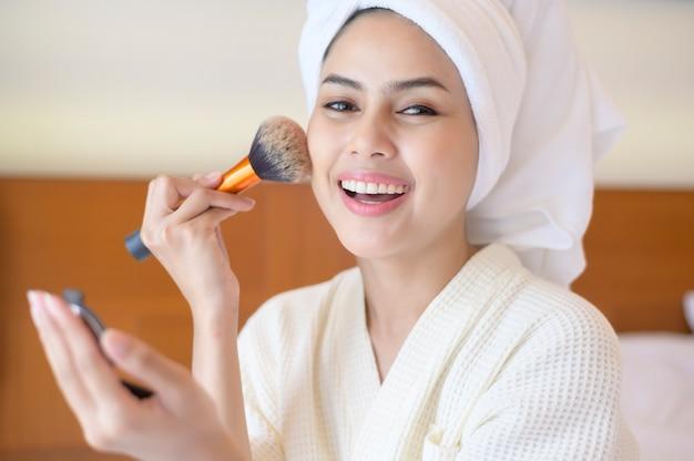 Atrakcyjna szczęśliwa kobieta w białym szlafroku nakłada naturalny makijaż z pędzelkiem kosmetycznym, beauty concept.