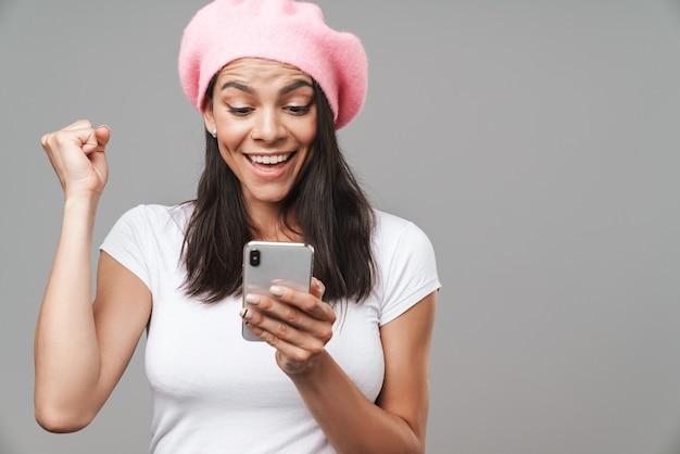 Atrakcyjna szczęśliwa młoda brunetka ubrana w beret stojący na białym tle nad szarą ścianą, trzymająca telefon komórkowy, świętująca sukces