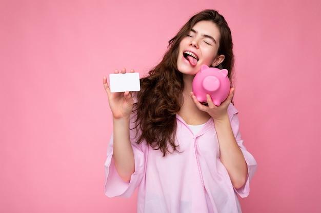 Atrakcyjna szczęśliwa młoda brunetka ubrana w koszulę na białym tle na różowym tle z pustą przestrzenią i