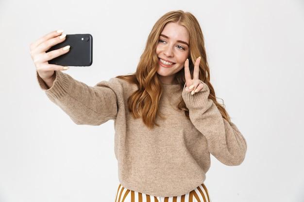 Atrakcyjna szczęśliwa młoda dziewczyna nosi sweter stojący na białym tle nad białą ścianą, biorąc selfie