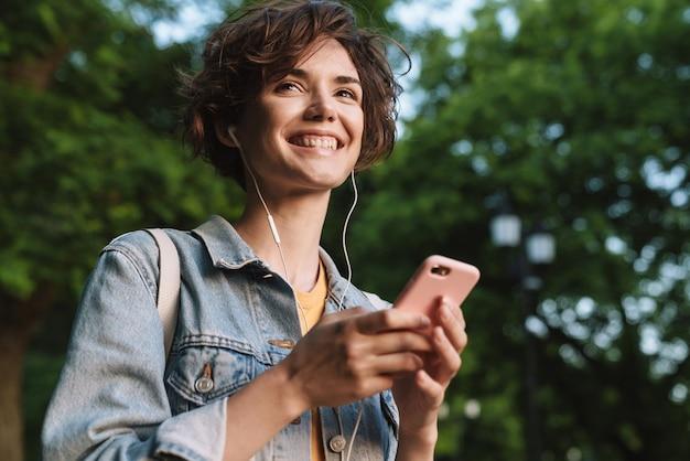 Atrakcyjna szczęśliwa młoda dziewczyna ubrana w swobodny strój, spędzająca czas na świeżym powietrzu w parku, słuchająca muzyki przez słuchawki, trzymająca telefon komórkowy